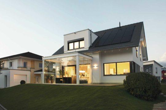 Musterhaus Balance 250 - Ein großes Backsteingebäude mit Gras vor einem Haus - WeberHaus