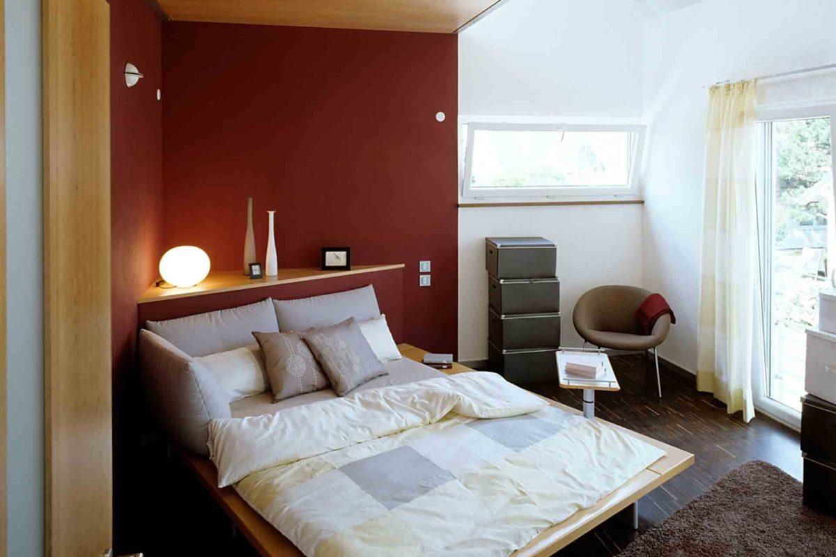 Musterhaus Mannheim - Ein Schlafzimmer mit einem Bett und einem Stuhl in einem Raum - Schlafzimmer