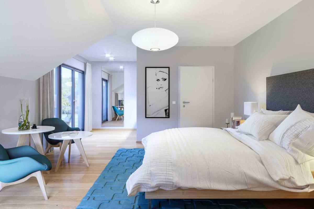 Musterhaus Mannheim - Ein Schlafzimmer mit einem Bett und einem Stuhl in einem Raum - Haus zeigen