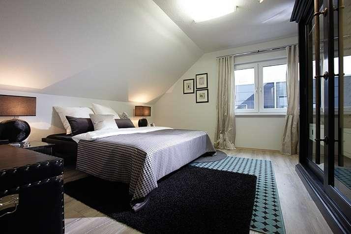 NEO 312 – Musterhaus Wuppertal (Aktionshaus) - Ein Schlafzimmer mit einem Bett und einem Schreibtisch in einem Hotelzimmer - FingerHaus