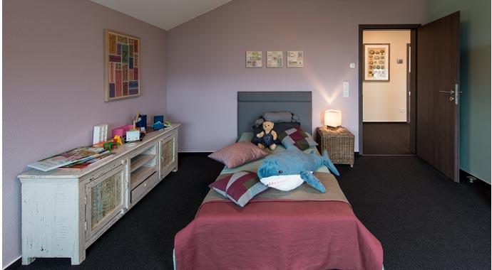 Aktionshaus MEDLEY 3.0 – Musterhaus Werder - Ein Schlafzimmer mit einem Bett und einem Schreibtisch in einem Raum - Schlafzimmer