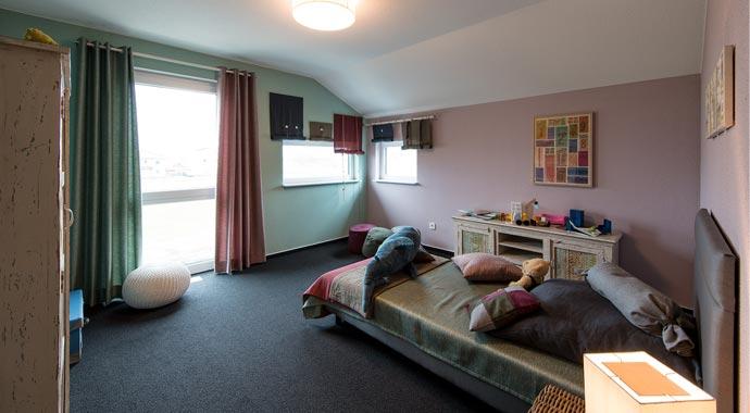 Aktionshaus MEDLEY 3.0 – Musterhaus Werder - Ein Wohnzimmer mit Möbeln und einem großen Fenster - FingerHaus