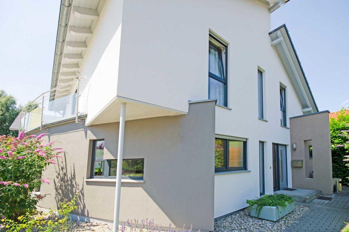 Musterhaus Pascino - Ein Haus mit Bäumen im Hintergrund - Haus