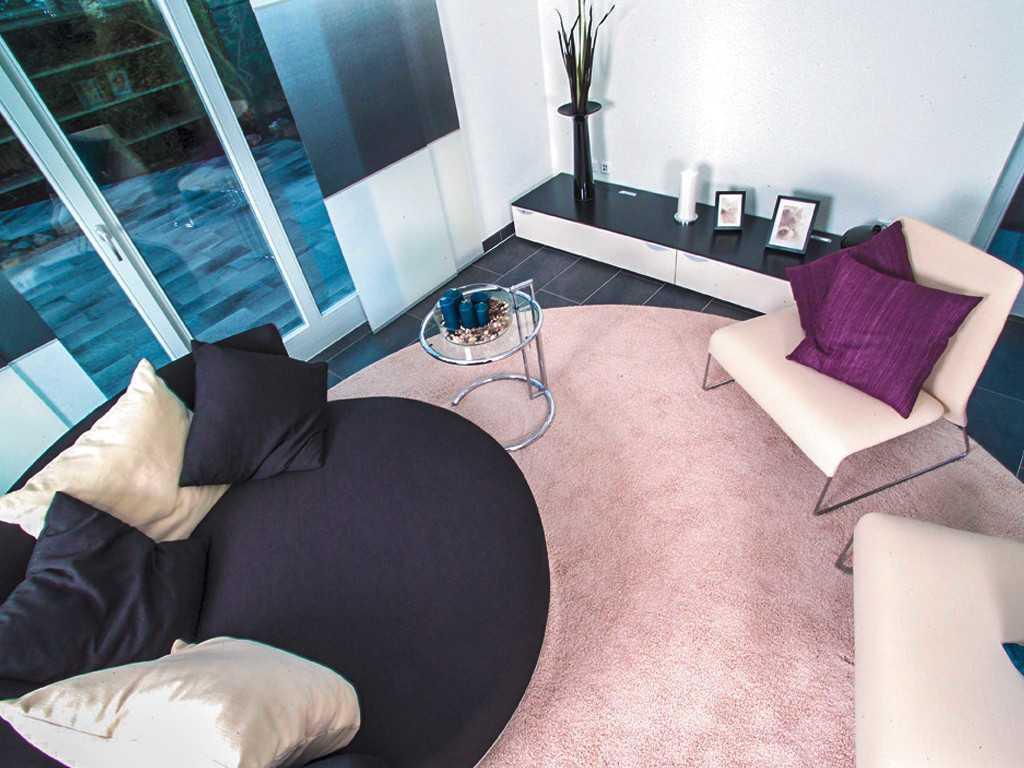 ProStyle 128 Musterhaus Mannheim - Ein Schlafzimmer mit einem Bett und einem Stuhl in einem Raum - Wohnzimmer