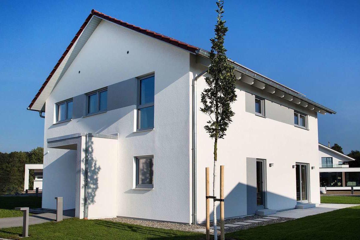 Musterhaus Günzburg - Ein Haus mit Bäumen im Hintergrund - Die Architektur