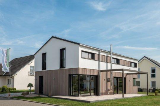 Automatisch gespeicherter Entwurf - Ein großes Backsteingebäude mit Gras vor einem Haus - Haus