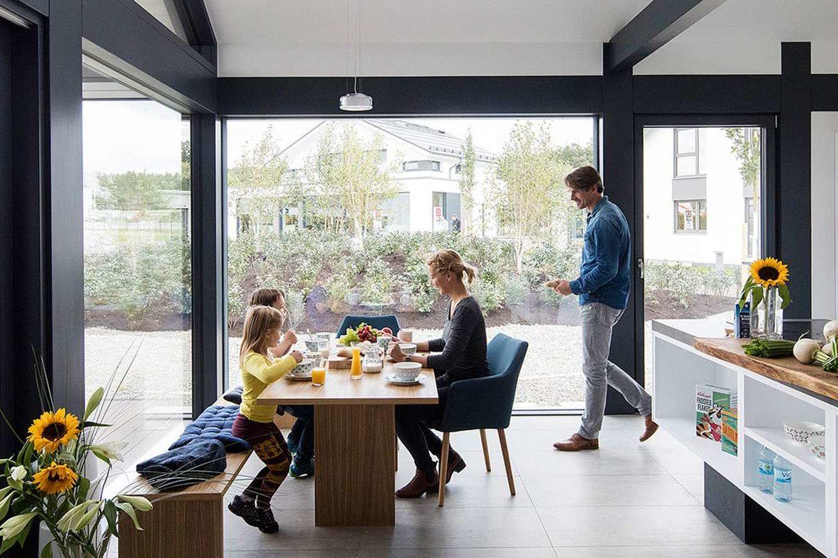 Musterhaus Günzburg - Eine Person, die an einem Tisch vor einem Fenster sitzt - Haus