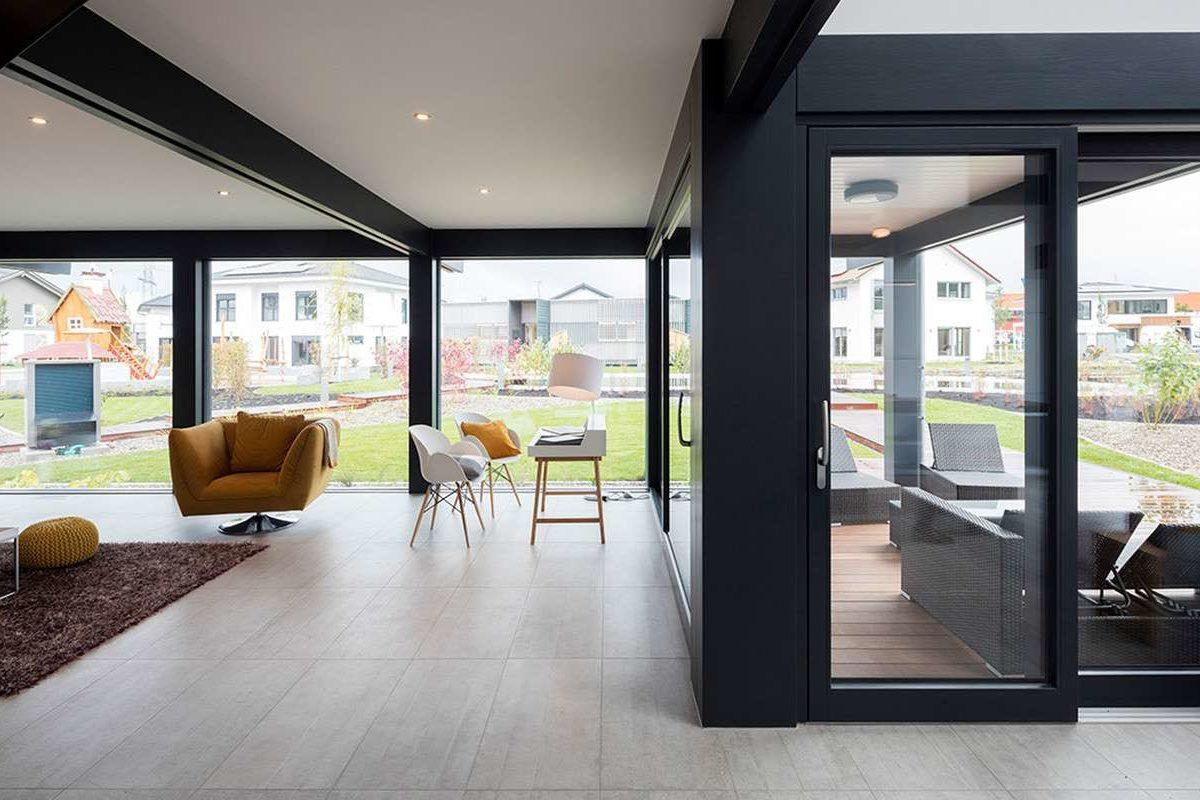 Musterhaus Günzburg - Eine Ansicht eines mit Möbeln gefüllten Wohnzimmers und eines großen Fensters - Die Architektur