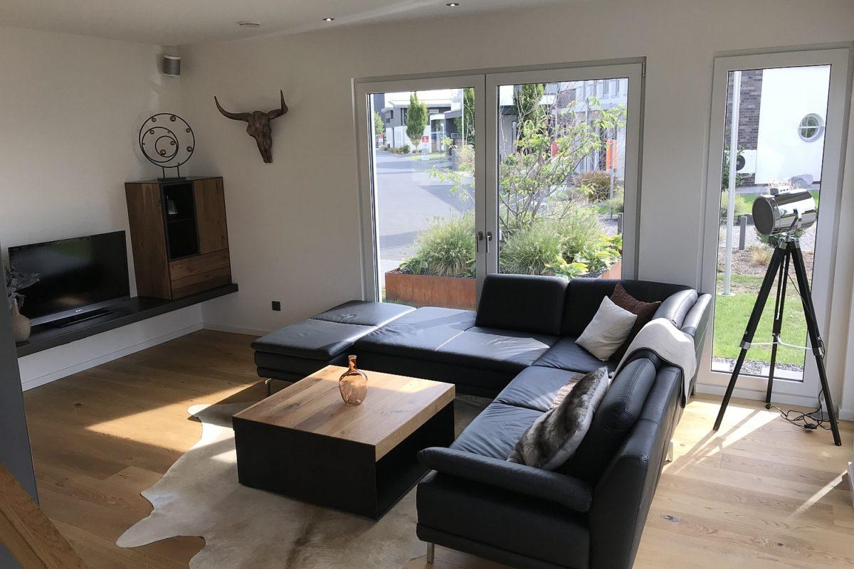 Musterhaus Köln - Ein Wohnzimmer mit Möbeln und einem großen Fenster - Interior Design Services