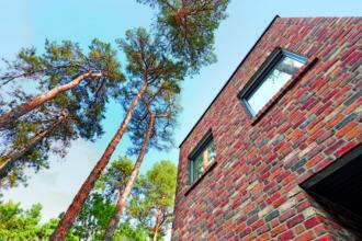 Außen Landhaus, innen Bauhaus - Ein hohes rotes Backsteingebäude - Fassade