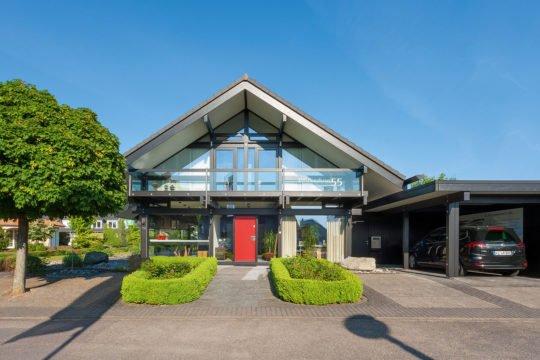 Automatisch gespeicherter Entwurf - Ein Haus mit Bäumen im Hintergrund - HUF HAUS Musterhaus Koblenz