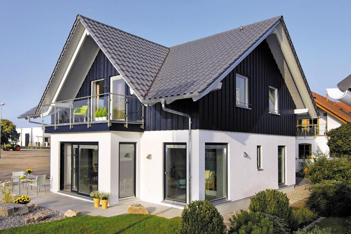 Musterhaus Offenburg - Ein großes Backsteingebäude mit Gras vor einem Haus - Haus