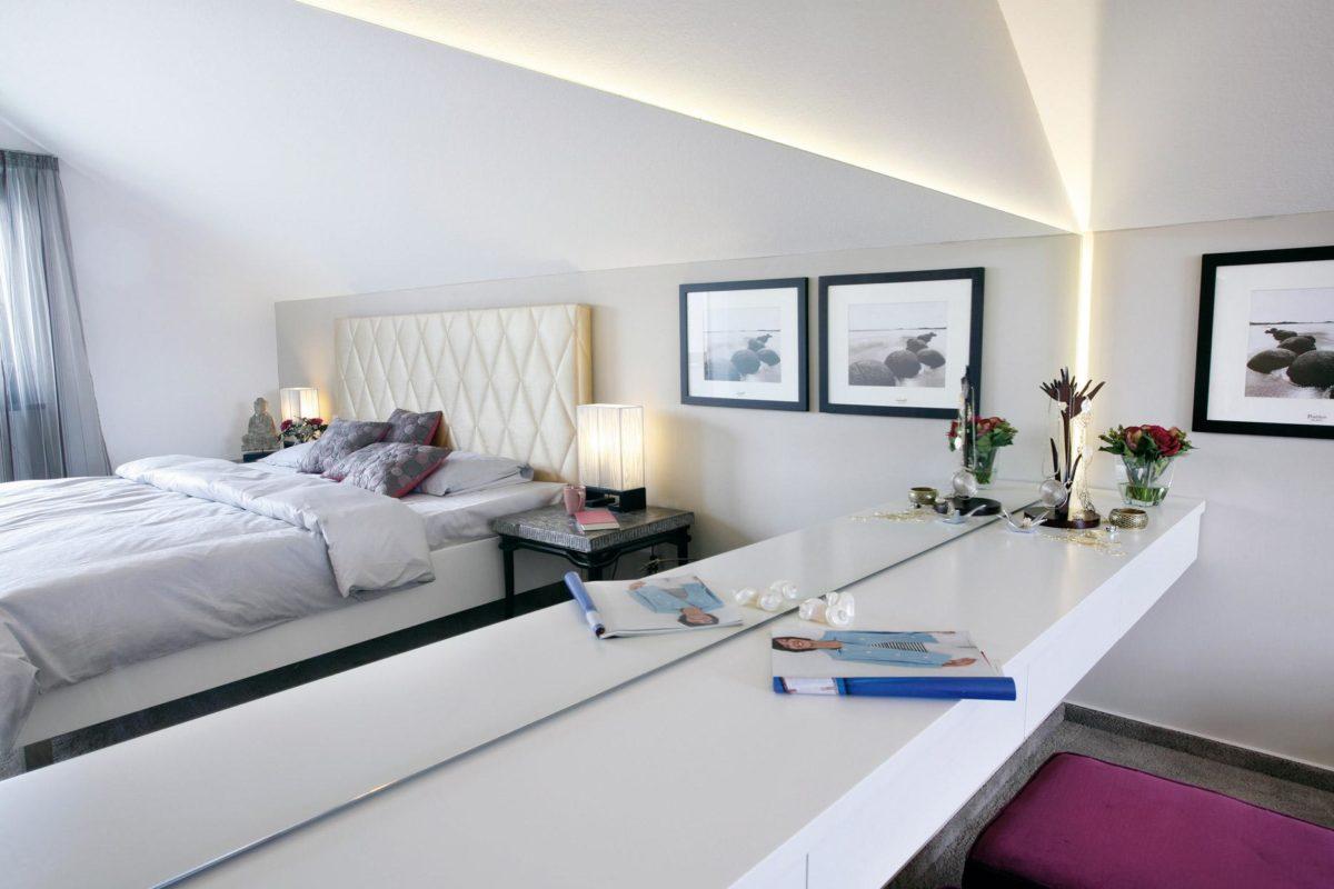 Musterhaus Hessdorf - Ein Schlafzimmer mit einem Bett und einem Schreibtisch in einem Raum - SchworerHaus KG
