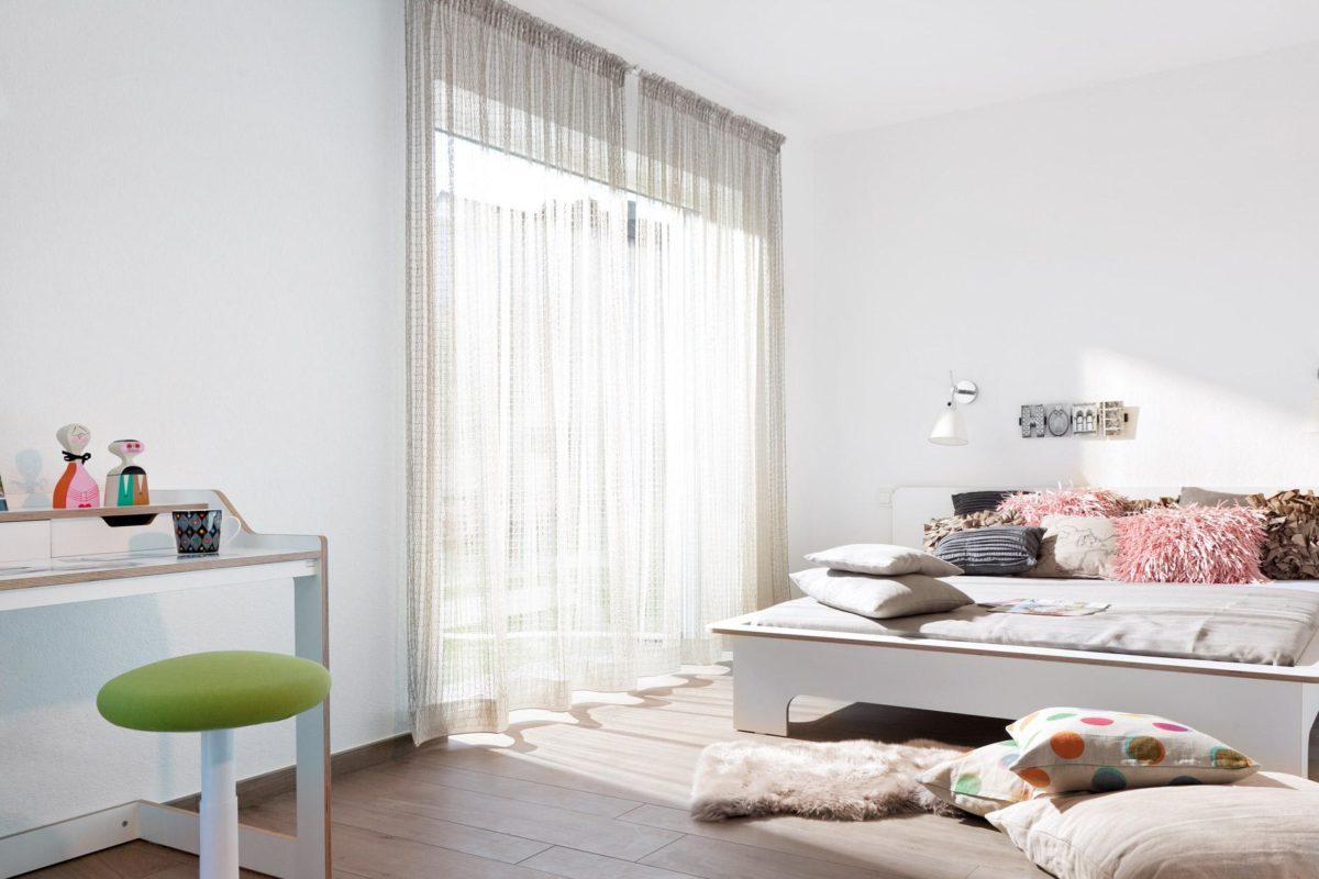 Kubushaus modern - Ein Schlafzimmer mit einem Bett und einem Stuhl in einem Raum - SchworerHaus KG