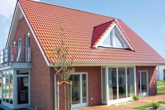 Automatisch gespeicherter Entwurf - Ein großes Backsteingebäude mit Gras vor einem Haus - Erkerfenster