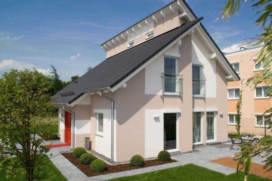 Musterhaus Jazz - Ein großes Backsteingebäude mit Gras vor einem Haus - Haus