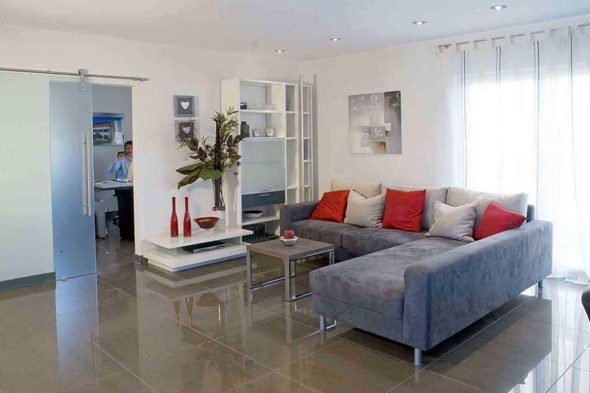 Musterhaus Jazz - Ein Wohnzimmer mit Möbeln und einem großen Fenster - Haus