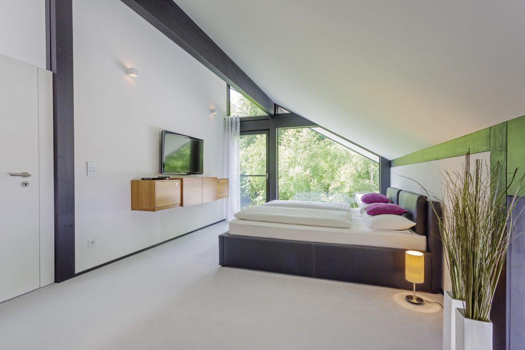 HUF HAUS MODUM 7 - Ein Schlafzimmer mit einem Bett in einem Raum - Interior Design Services