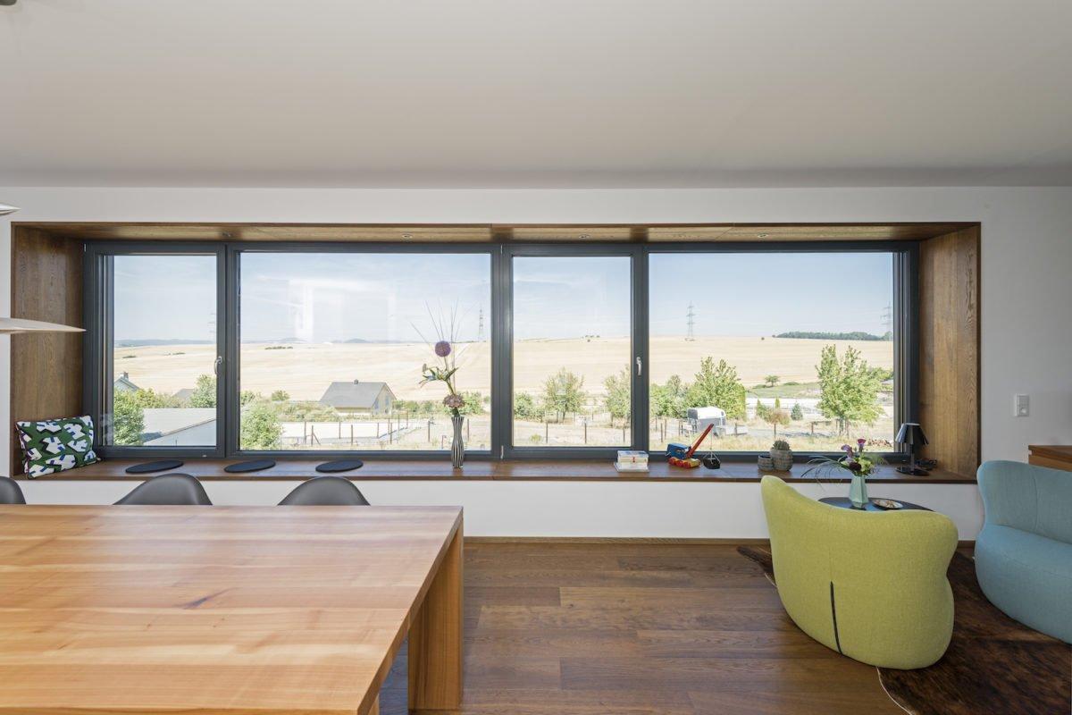 Kundenhaus Schaub - Ein Wohnzimmer mit Möbeln und einem großen Fenster - Interior Design Services