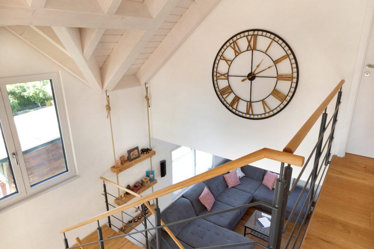 Kundenhaus U237 - Ein Raum mit einer Uhr auf einem Holztisch - Holzboden
