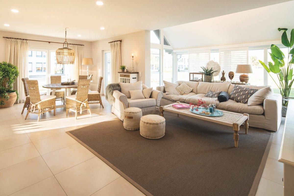 Musterhaus Juno - Ein Wohnzimmer mit Möbeln und einem Kamin - Interior Design Services