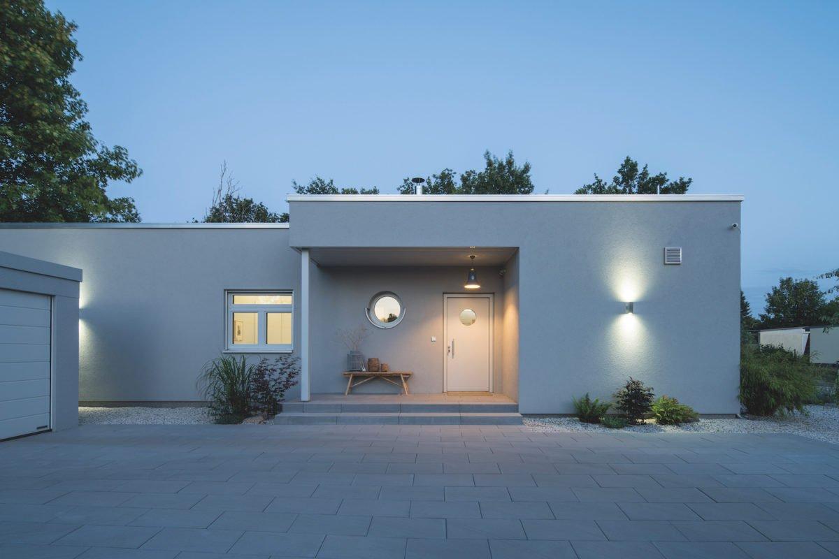 Kundenhaus NIVO - Ein Haus mit Bäumen im Hintergrund - Die Architektur