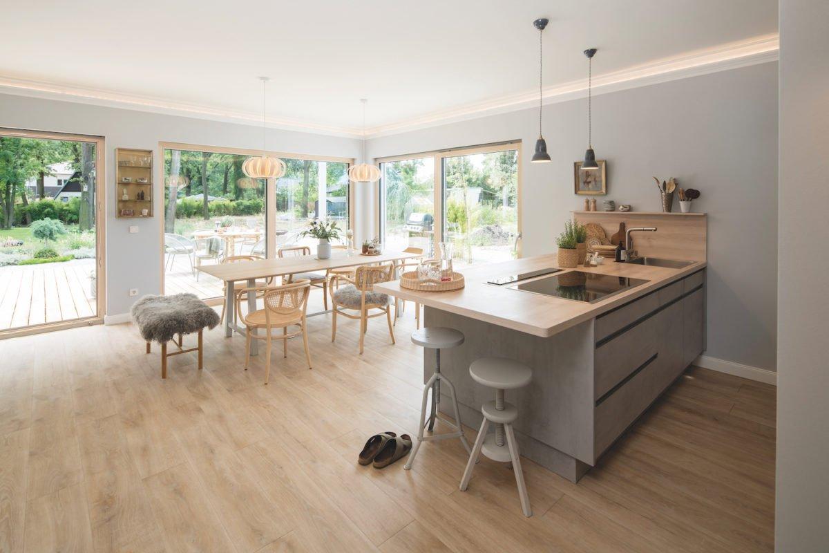 Kundenhaus NIVO - Ein Wohnzimmer mit Möbeln und einem großen Fenster - Interior Design Services