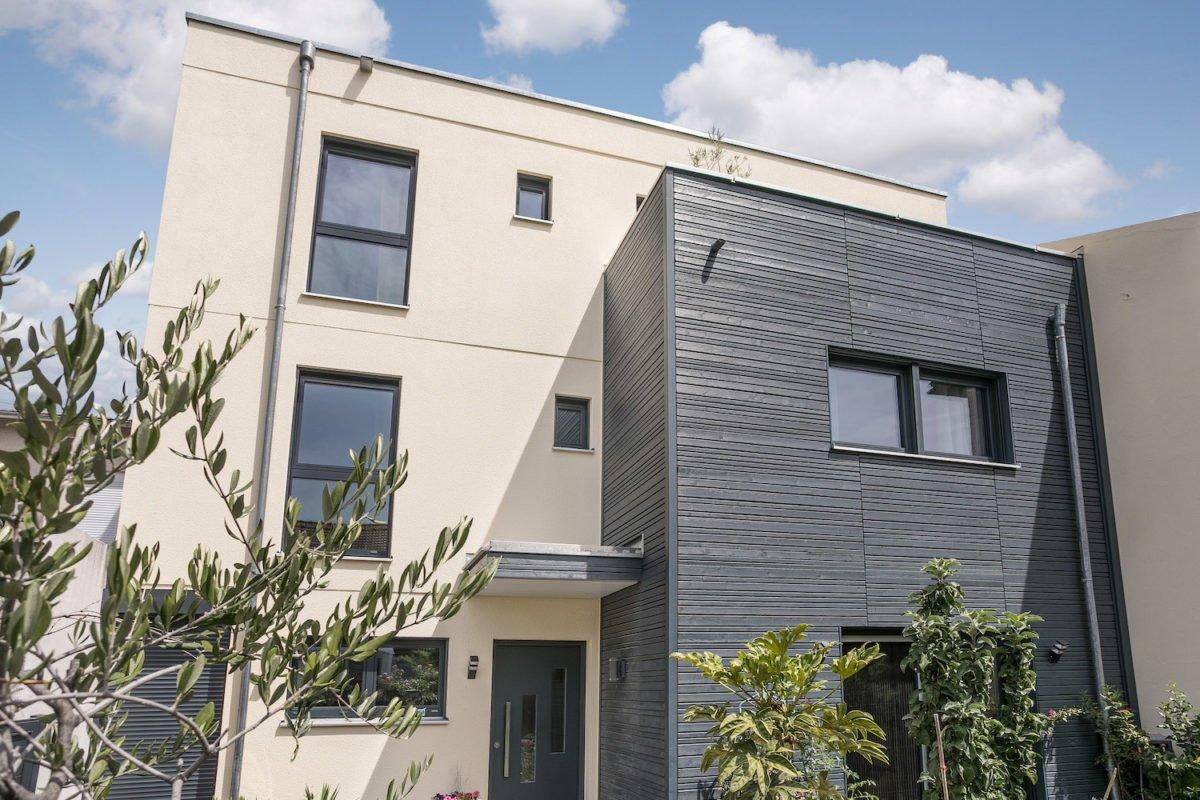 Kundenhaus Oliveira - Ein Haus mit Bäumen vor einem Gebäude - Fassade