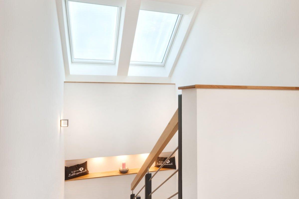 Haus U120 - Ein Schlafzimmer mit einem Bett und einem Spiegel - Holz